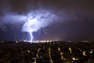 A flash of lighting is seen in Piraeus, near Athens during a rainstorm on Friday, Feb. 22, 2013. Hours of heavy rainfall in Athens caused extensive flooding, inundating basements and forcing authorities to close major roads and a central subway station. The Greek fire brigade says it received more than 900 calls to pump out water in the greater Athens region Friday. (AP Photo/Fosphotos, Elina Liberta)