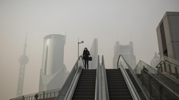 A woman wears a surgical mask during a hazy day in Shanghai's financial district of Pudong