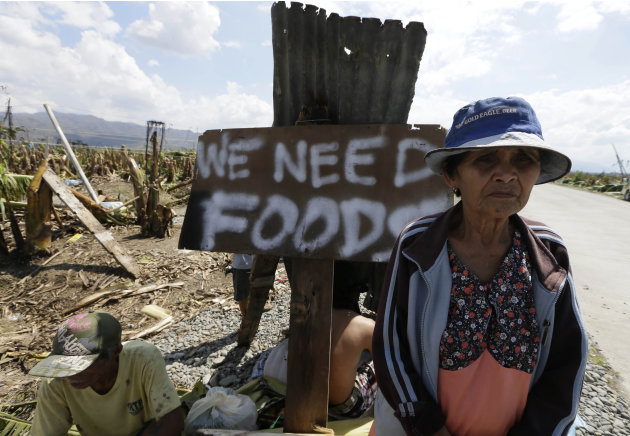 Residents affected by typhoon Bopha beg for aid from passing motorists along a highway at Montevista township, Compostela Valley in southern Philippines Sunday Dec. 9, 2012. The number of missing in t