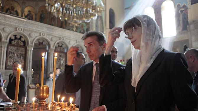 Georgia's billionaire and opposition leader Bidzina Ivanishvili, left, and his wife Ekaterine Khvedelidze pray in a church in Tbilisi, Georgia, Monday, Oct. 1, 2012. Voters in Georgia are choosing a new parliament in a heated election Monday that will decide the future of Saakashvili's government. (AP Photo/Georgy Abdaladze)