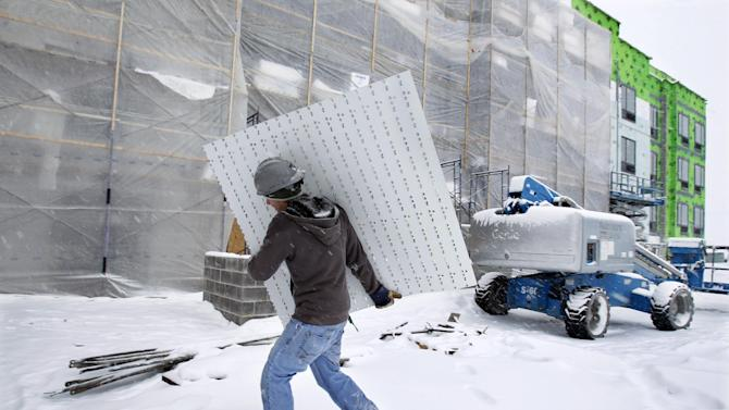 Worker Steve Rizzo carries materials in a snowfall at a new hotel construction in Buffalo, N.Y., Saturday, Dec. 29, 2012. A mild but widespread winter storm has developed over the Northeast and the upper Ohio River Valley, the second in less than a week for the regions. (AP Photo/Mel Evans)
