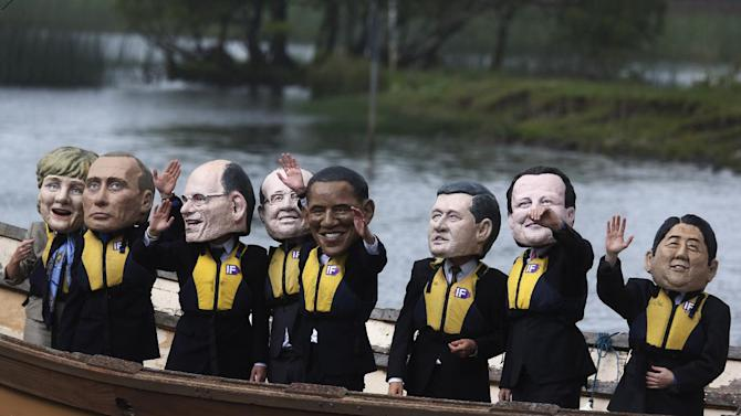 Anti-hunger activists, wearing giant head masks depicting the G-8 leaders, sail on a boat past the hotel where the G8 summit media center is located in Enniskillen, Northern Ireland, on Monday, June 17. The protesters, from the Enough Food for Everyone IF campaign, call for leaders to eliminate the causes of hunger. G-8 leaders depicted are, from right to left, Japanese Prime Minister Shinzo Abe, British Prime Minister David Cameron, Canadian Prime Minister Stephen Harper, U.S. President Barack Obama, French President Francois Hollande, Italian Prime Minister Enrico Letta, Russian President Vladimir Putin, and German Chancellor Angela Merkel. (AP Photo/Lefteris Pitarakis)