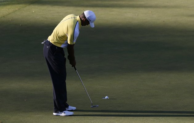 Woods of the U.S. sinks a bogey putt on the 15th green during second round play in the 2013 Masters golf tournament in Augusta