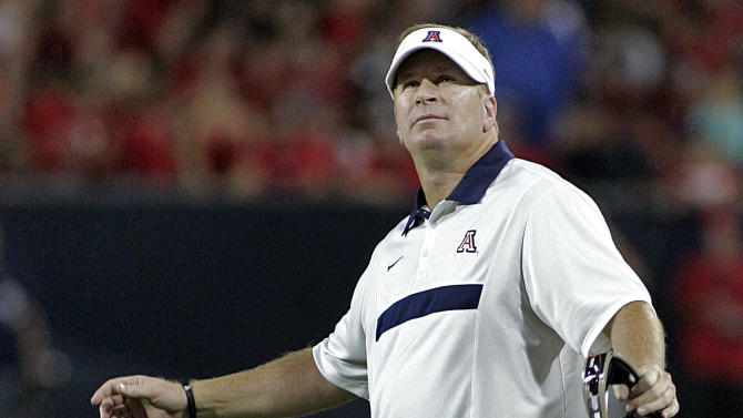 FILE - In this Sept. 3, 2011, file photo, Arizona head football coach Mike Stoops looks at the stadium video screen during the first half against Northern Arizona in an NCAA college football game at Arizona Stadium in Tucson, Ariz. (AP Photo/John Miller, File)