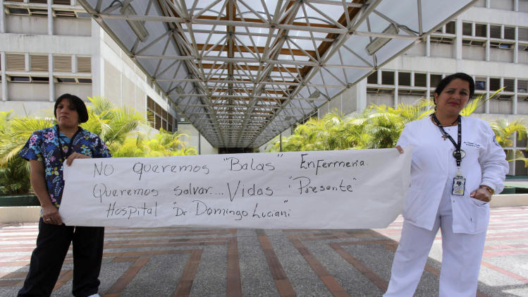 "In this Aug. 26, 2011 photo, nurses holds a poster that reads in Spanish, ""We don't want bullets, we want to save lives - Dr. Domingo Luciani Hospital,"" as they demonstrate outside the hospital in Caracas, Venezuela. Bullets tore up the emergency ward of the Domingo Luciani Hospital in Caracas on Aug. 20, 2011. Employees said relatives and friends of a young man who died of gunshot wounds were enraged when they learned he had died and opened fire. Everyone escaped uninjured, and National Guard troops arrested the group that opened fire. (AP Photo/Fernando Llano)"