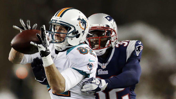Miami Dolphins wide receiver Brian Hartline (82) catches a pass in front of New England Patriots free safety Devin McCourty (32) during the second quarter of an NFL football game in Foxborough, Mass., Sunday, Dec. 30, 2012. (AP Photo/Elise Amendola)