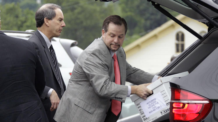 Attorneys for former Penn State University assistant football coach Jerry Sandusky, Joe Amendola, left, and Karl Rominger, unload case files after arriving at the Centre County Courthouse in Bellefonte, Pa., Monday, June 18, 2012. The defense is to begin presenting it's case in Sandusky's trial on 52 counts of child sexual abuse involving 10 boys over a period of 15 years on Monday. (AP Photo/Gene J. Puskar)