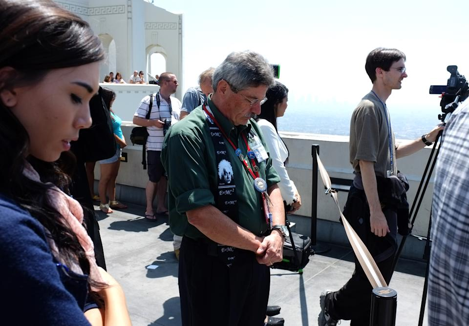 Robert Spellman, telescope demonstrator at the Griffith Observatory, joins visitors in a minute of silence for astronaut Neil Armstrong in Los Angeles on Saturday, Aug. 25, 2012. Armstrong died on Saturday. (AP Photo/Richard Vogel)