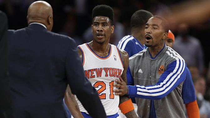 New York Knicks' Iman Shumpert, center, is restrained by J.R. Smith, right, and coach Mike Woodson during an argument with the Indiana Pacers in the first half of Game 5 of an Eastern Conference semifinal in the NBA basketball playoffs, at Madison Square Garden in New York, Thursday, May 16, 2013. (AP Photo/Julio Cortez)