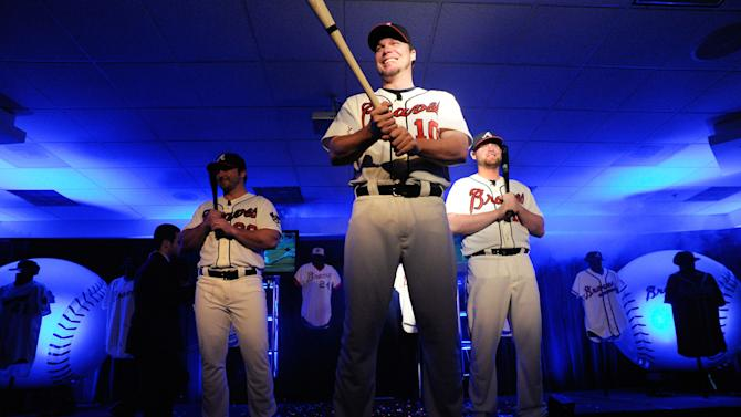 Atlanta Braves' Chipper Jones, center, Brian McCann, right, and Dan Uggla model the club's new alternative home uniform during a news conference to introduce the new threads, Monday, Feb. 6, 2012, in Atlanta. The uniform pays homage to the team's past, reflecting more of the look of the 1966 team. (AP Photo/John Amis)