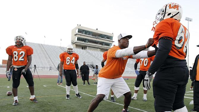 IMAGE DISTRIBUTED FOR DURACELL - Dallas defensive lineman DeMarcus Ware coaches senior offensive lineman Markel Garner (62) during the Lancaster Tiger practice on Tuesday, Nov. 13, 2012inLancaster, Texas. DeMarcus joined Duracell Trust Your Power program to encourage youth to realize their power to achieve their goals. (Photo by Brandon Wade/Invision for Duracell/AP Images)