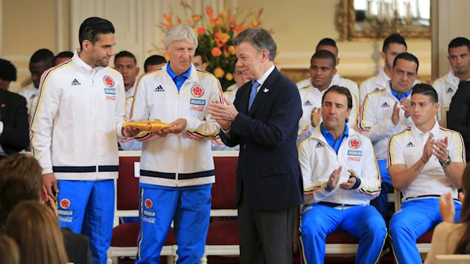 Santos applauds after handing the national flag to Garcia and Pekerman during a ceremony at presidential palace in Bogota