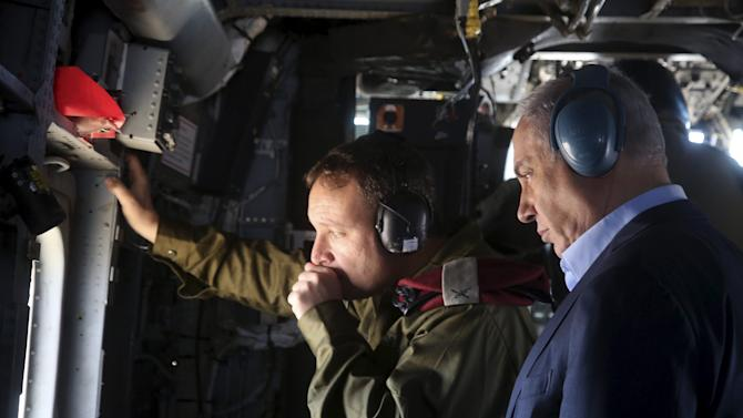 Israeli Prime Minister Benjamin Netanyahu looks out of a military airplane as he makes his way to visit the border fence between Israel and Jordan