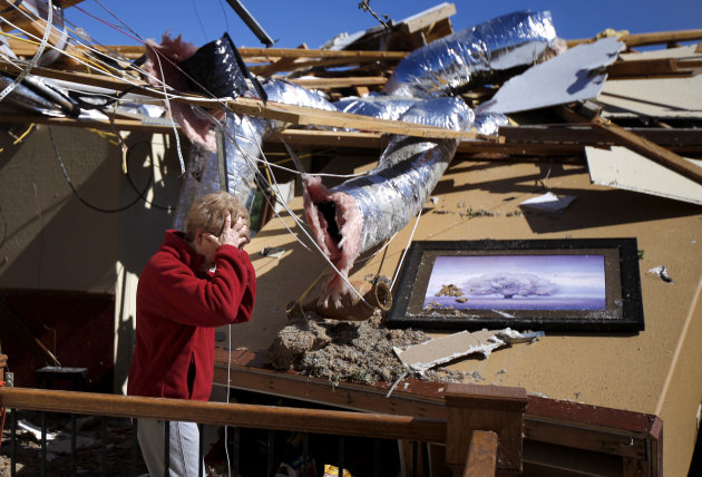 Carole Beckett reacts as she sorts through belongings at her home after a tornado moved through Woodward, Okla., Sunday, April 15, 2012.  Residents of several states scoured through the wreckage of ba