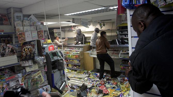 People loot a shop in Hackney, east London, Monday, Aug. 8, 2011. Violence and looting spread across some of London's most impoverished neighborhoods on Monday, with youths setting fire to shops and vehicles, during a third day of rioting in the city that will host next summer's Olympic Games. (AP Photo/PA, Lewis Whyld) UNITED KINGDOM OUT, NO SALES, NO ARCHIVE