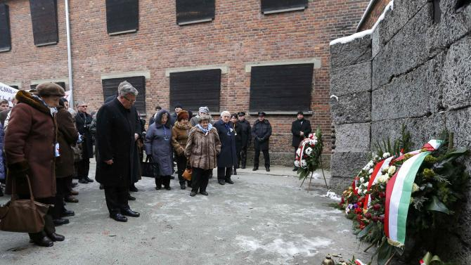 Polish President Komorowski bows as he lays a wreath at the 'Wall of Death' in the former Nazi German concentration and extermination camp Auschwitz in Oswiecim