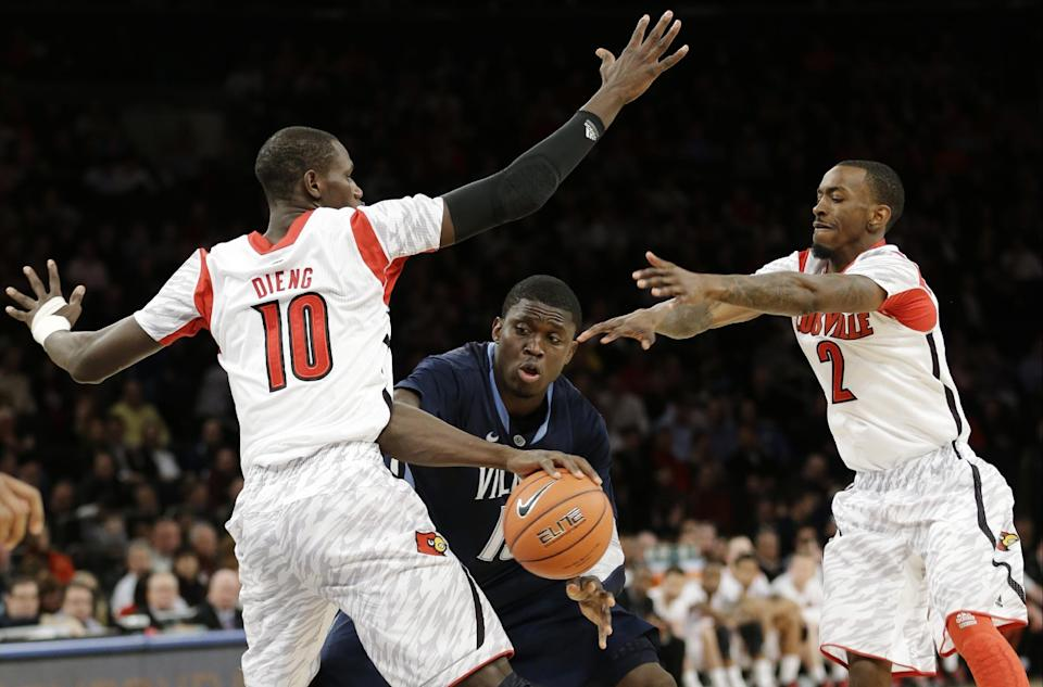 Villanova's Mouphtaou Yarou (13) is defended by Louisville's Gorgui Dieng (10) and Russ Smith (2) during the second half of an NCAA college basketball game at the Big East Conference tournament, Thursday, March 14, 2013, in New York. (AP Photo/Frank Franklin II)