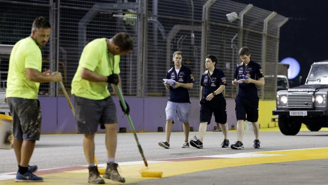 Red Bull Formula One driver Vettel of Germany and crew members walk on the the Marina Bay street circuit as workers put finishing touches to the circuit ahead of Singapore F1 Grand Prix in Singapore