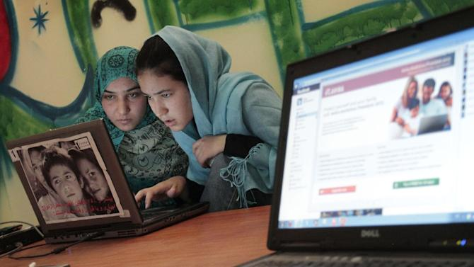 In this Monday, July 30, 2012 photo Regwida Neayish 19, right, surfs the Internet with a friend at the Sahar Gul Internet cafe in Kabul, Afghanistan. Donor nations have pledged to keep bankrolling the Afghan security forces and send more development money, but none of this has done much to raise the hopes of many Afghans who remain in deep despair about the future of their nation after international troops leave. (AP Photo/Musadeq Sadeq)