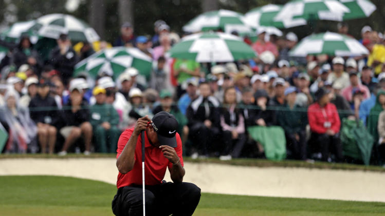 Tiger Woods waits to putt on the 18th green during the fourth round of the Masters golf tournament Sunday, April 14, 2013, in Augusta, Ga. (AP Photo/David J. Phillip)