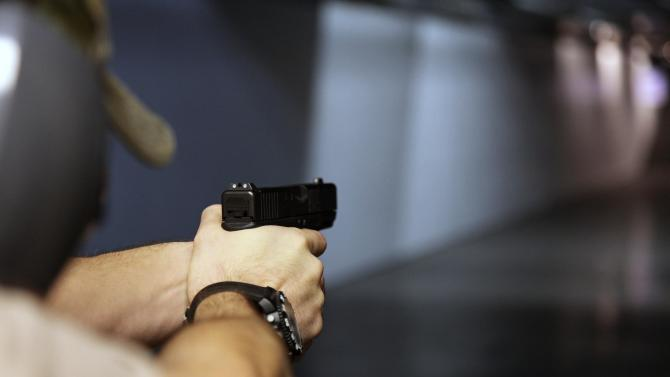 In this Jan. 4, 2013, photo, a man fires a hand gun at Sandy Springs Gun Club and Range, in Sandy Springs, Ga. In Connecticut and Colorado, scenes of the most deadly U.S. mass shootings in 2012, people were less enthusiastic about buying new guns at the end of the year than in most other states, according to an Associated Press analysis of new FBI data. The biggest surges in background checks for people who want to carry or buy guns occurred in states in the South and West. (AP Photo/Robert Ray)