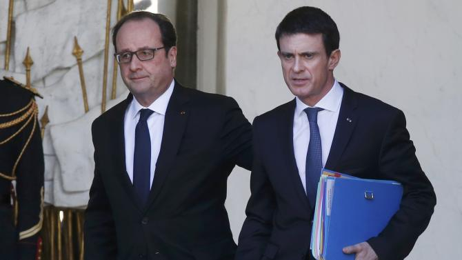 French Prime Minister Manuel Valls talks to French President Francois Hollande as he leaves the Elysee Palace following the weekly cabinet meeting in Paris