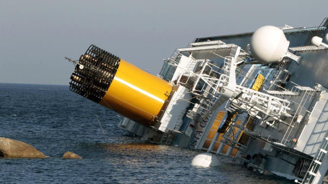 The luxury cruise ship Costa Concordia leans on the rocks after running aground the tiny Tuscan island of Giglio, Saturday, Jan. 14, 2012. A luxury cruise ship ran aground off the coast of Tuscany, sending water pouring in through a 160-foot (50-meter) gash in the hull and forcing the evacuation of some 4,200 people from the listing vessel early Saturday, the Italian coast guard said. (AP Photo/Gregorio Borgia)