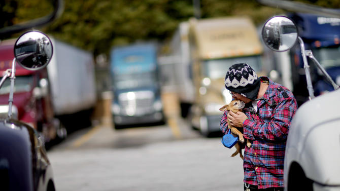 Truck driver Jimmy Mayes holds his chihuahua, Coco, while waiting to pick up a load at a truck stop Tuesday, Oct. 30, 2012, in Atlanta. Even amid a struggling economy with high unemployment, trucking companies had a tough time hiring young drivers willing to hit the road for long hauls. Now the U.S. is speeding toward a critical shortage of truck drivers in the next few years as the economy recovers and demand for goods increases, an expert in the inner-workings of supply chains said in a report Tuesday. (AP Photo/David Goldman)