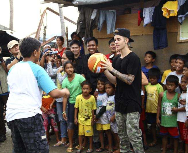 "Justin Bieber plays basketball with children survivors of Typhoon Haiyan during his unannounced visit Tuesday, Dec. 10, 2013 at Tacloban city, Leyte province in central Philippines. The teen heartthrob Bieber arrived Tuesday in the Philippines, where he has launched a campaign to help victims of last month's killer typhoon. Bieber, adored by young fans worldwide for hits like ""Baby,"" arrived on a special flight, Immigration officer Jerome Ollet said. (AP Photo)"