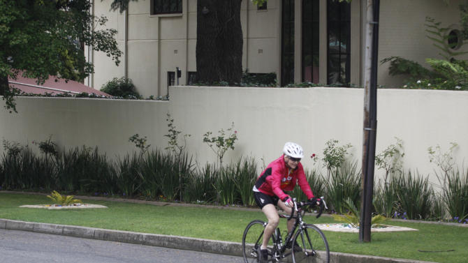 A person cycles past the home of former President Nelson Mandela in Johannesburg, Thursday, Dec. 27 2012 after Mandela's discharge from a Pretoria hospital Wednesday, Dec. 26.  Mandela was released Wednesday from the hospital after being treated for a lung infection and having gallstones removed, a government spokesman said. But the 94-year-old anti-apartheid icon will continue to receive medical care at home. (AP Photo/Denis Farrell)