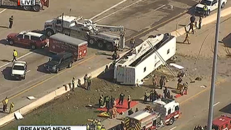 This frame grab provided by KXAS-TV shows emergency personnel at the scene where a chartered bus overturned on a highway near Dallas-Fort Worth International Airport in Irving, Texas.  Authorities say at least six people are hospitalized.  (AP Photo/Courtesy KXAS-TV) MANDATORY CREDIT
