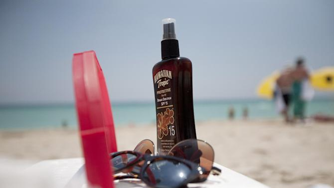 This Wednesday, May 9, 2012 photo shows a bottle of sun tan lotion and sunglasses on top of a cooler carried onto Miami Beach, Fla. by tourists. In a study released Thursday, May 10, 2012, the Centers for Disease Control and Prevention says half of adults under 30 say they've had a sunburn at least once in the past year. Experts worry it's a sign young people aren't paying much attention to warnings about skin cancer, including the deadliest kind. (AP Photo/J Pat Carter)
