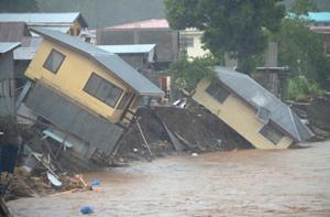 Flood waters run past damaged homes in the Solomon …