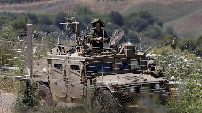 In this picture taken on Thursday May 23, 2013, Israeli soldiers patrol on their side of the Lebanese-Israeli border of Hamames village, Lebanon. In the eerily quiet south, the Hezbollah battle in the Syrian town of Qusair seems far away as most residents of towns and villages nervously watch Israeli army patrols drive along the border, their bases tucked away just behind a metal fence. Hezbollah's very public _ and bloody _ foray into Syria's war emboldened the group's critics in the Arab world and its Western-backed political opponents in Lebanon, futher fragmenting the national unity that was last forged by Hezbollah when it fought Israel to a standstill in 2006. (AP Photo/Hussein Malla)