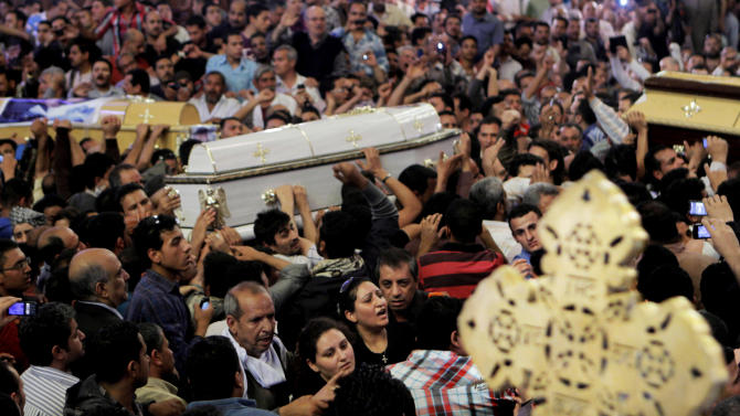 Egyptian Christians four coffins during a funeral service, at the Saint Mark Coptic cathedral in Cairo, Egypt, Sunday, April 7, 2013. Several Egyptians including 4 Christians and a Muslim were killed in sectarian clashes before dawn in Qalubiya, just outside of Cairo on Saturday, April 6, 2013. (AP Photo/Amr Nabil)