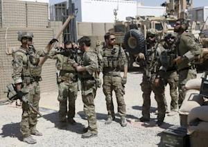 U.S. special forces soldiers talk to each other before…