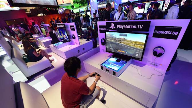 People test the new Playstation TV at the E3 video game extravaganza in Los Angeles, California, on June 10, 2014