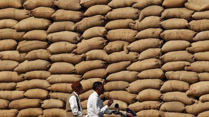 Farmers ride on a motorbike in front of stacked sacks filled with grains at APMC market yard on the outskirts of Ahmedabad