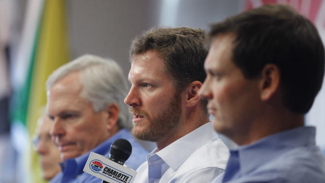 Dale Earnhardt Jr, center, talks about missing the next two races with his second concussion in the past six weeks as team owner Rick Hendrick, left, and crew chief Steve Letarte, right, look on  during a news conference prior to practice for Saturday's NASCAR Bank of America 500 NASCAR Sprint Cup series auto race in Concord, N.C., Thursday, Oct. 11, 2012. (AP Photo/Chuck Burton)