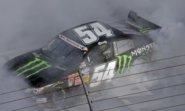 Kyle Busch (54) is engulfed in smoke as he does a burnout after winning the NASCAR Nationwide Series auto race at the Charlotte Motor Speedway in Concord, N.C., Saturday, May 25, 2013. (AP Photo/Gerry