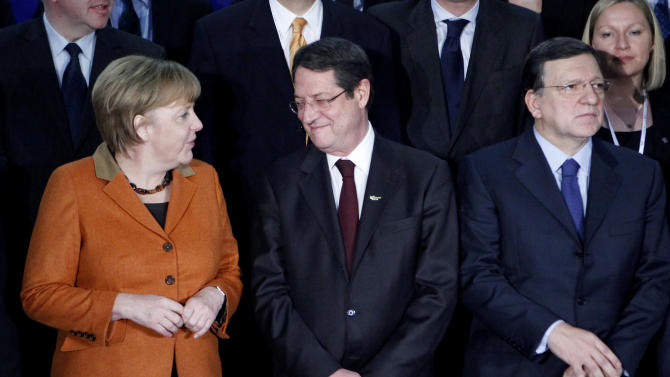 German Chancellor Angela Merkel, and opposition Democratic Rally party leader Nicos Anastasiades talk as EU Commission President Jose Manuel Barosso looks on during a group photo before a European People's Party (EEP) meeting in Cyprus' southern coastal resort of Limassol in an extraordinary summit on Friday, Jan. 11, 2013. Among the topics of discussion at the meeting hosted by the leader of Cyprus' main opposition Democratic Rally party Nicos Anastasiades will be the EU budget. Anastasiades is currently leading opinion polls as the top contender ahead of the country's Feb. 17 presidential election. Cyprus is in the midst of talks with international lenders on a bailout to rescue its ailing banking sector that sustained massive losses on bad Greek debt and loans. (AP Photo/Petros Karadjias)