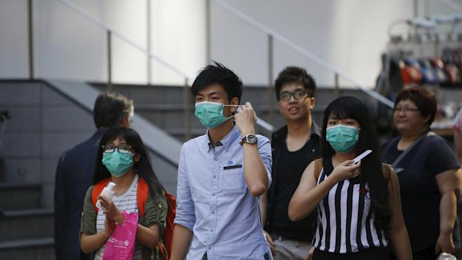 Tourists wearing masks to prevent contracting Middle East Respiratory Syndrome (MERS), walk at Myeongdong shopping district in central Seoul