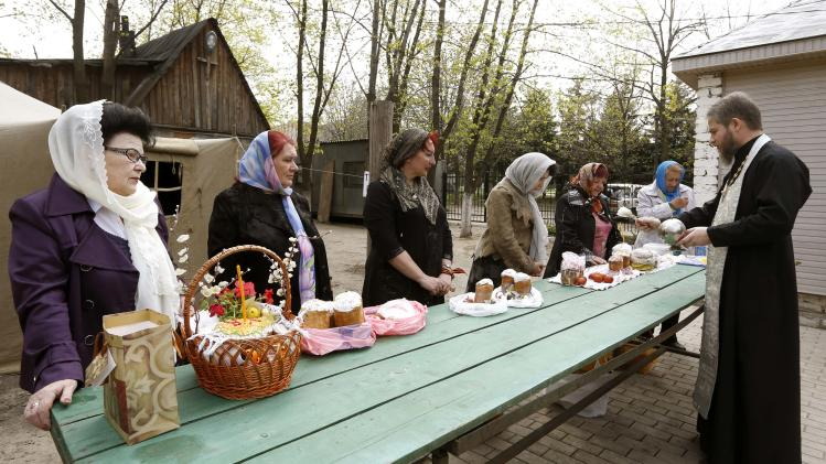 "An Orthodox priest sprinkles holy water on believers and their ""paskha"" cakes, eggs and other food on the eve of Easter at the Orthodox church in Luhansk"