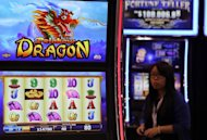 A woman walks past gaming machines at the G2E Asia gaming expo in Macau on May 22, 2012. The casino industry is booming across Asia, offering anyone looking for high-stakes action a wide choice of venues, from high-tech South Korea to the Himalayan nation of Nepal and communist Vietnam