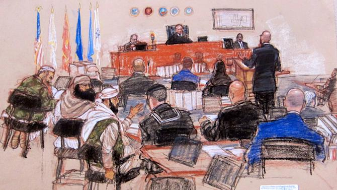 In this pool photo of a sketch by courtroom artist Janet Hamlin and reviewed by the U.S. Department of Defense, the self-proclaimed terrorist mastermind Khalid Sheikh Mohammed, far left, accused co-conspirators Walid bin Attash, second from left, and Ramzi Binalshibh, fourth from left, sit with their legal teams as defense lawyer James Connell, standing at right, interrogates courtroom technology manager Maurice Elkins, top right, who testifies in the pre-trial hearing of the death penalty case against the five Sept. 11 defendants at the Guantanamo Bay U.S. Naval Base in Cuba, Tuesday, Feb. 12, 2013. Elkins, the official in charge of the sound system at the Guantanamo Bay war crimes tribunal, testified Tuesday that the microphones used by attorneys inside the courtroom have been changed so they will no longer be live unless they are manually activated to address the concerns of the defense.  (AP Photo/Janet Hamlin, Pool)