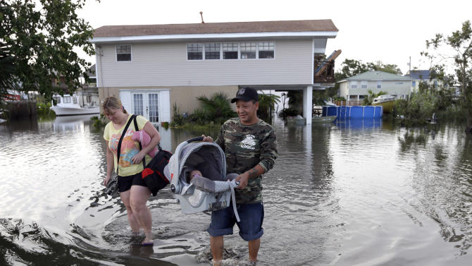 Tony Rodriguez, right, carries his baby daughter Nicole as they and his wife Jodi Clelland leave their flooded home in the aftermath of Hurricane Isaac in Slidell, La., Friday, Aug. 31, 2012. Isaac is now a tropical depression and the center was on track to cross Arkansas on Friday and southern Missouri on Friday night, spreading rain as it goes. (AP Photo/David J. Phillip)