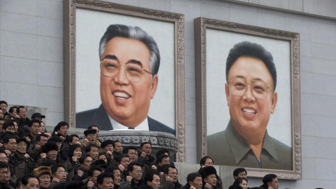 North Koreans chant slogans and gesture to show their determination near giant portraits of the late leaders Kim Il Sung, left, and Kim Jong Il during a mass rally organized to celebrate the success of a rocket launch that sent a satellite into space, on Kim Il Sung Square in Pyongyang, North Korea, Friday, Dec. 14, 2012. As the U.S. led international condemnation of what it calls a covert test of missile technology, top North Korean officials denied the allegations and maintained the country's right to develop its space program. (AP Photo/Ng Han Guan)