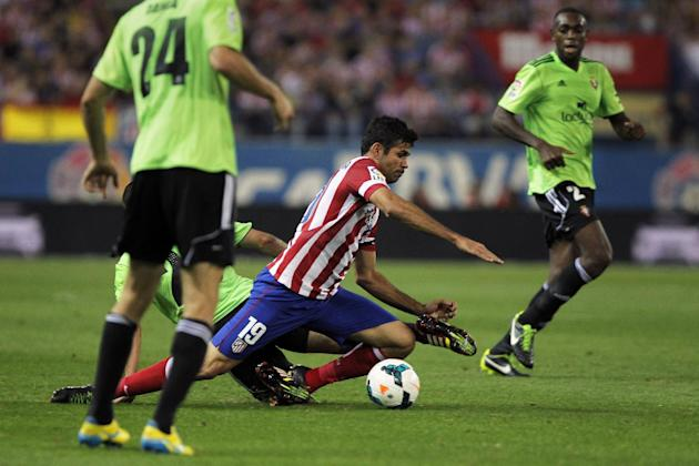 Atletico de Madrid's Diego Costa from Brazil, centre controls the ball in between Osasuna's palyers during a Spanish La Liga soccer match at the Vicente Calderon stadium in Madrid, Spain, Tuesday, Sep