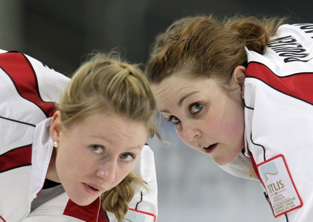 Denmark's Simonsen and Poulsen watch a stone during their World Women's Curling Championship qualification round against Germany in Riga