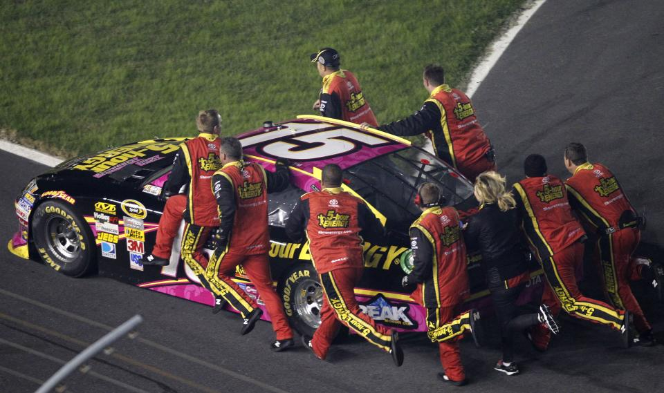 Crew members for Clint Bowyer push his car to victory lane after winning the NASCAR Bank of America 500 Sprint Cup series auto race in Concord, N.C., Saturday, Oct. 13, 2012. Bowyer ran out of gas while doing a burnout. (AP Photo/Terry Renna)